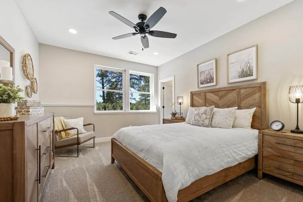 This bedroom is furnished with a wooden dresser, cushioned armchair, and a cozy bed flanked by matching nightstands.