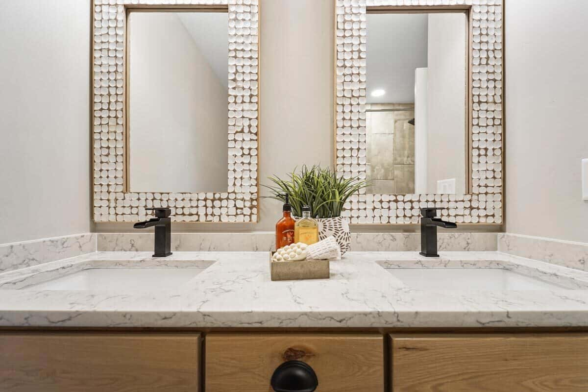 A close-up look at the marble top vanity with dual sink, wrought iron faucets, and decorative mirrors.