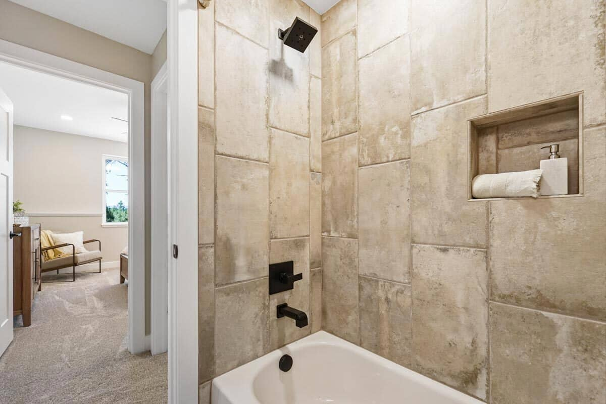 A shower and tub combo with tiled walls, wrought iron fixtures, and an inset shelf.