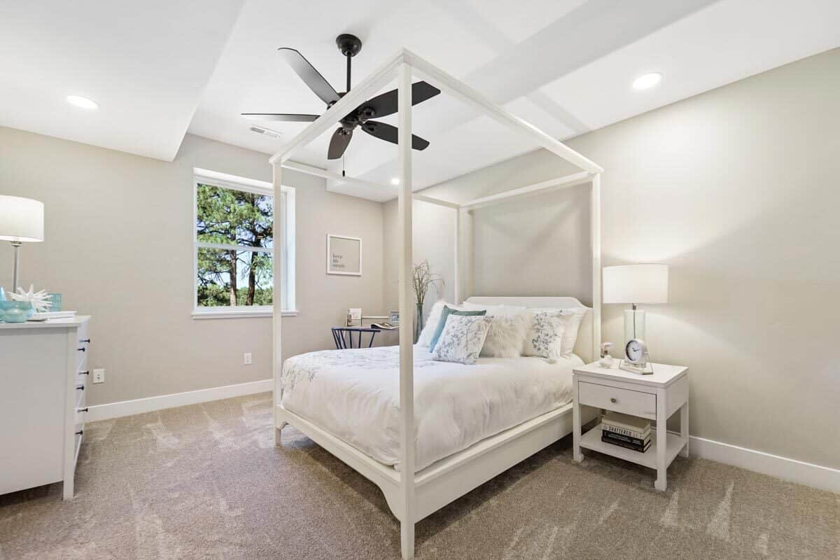 Another bedroom with a canopy bed, white dresser, and a picture window.