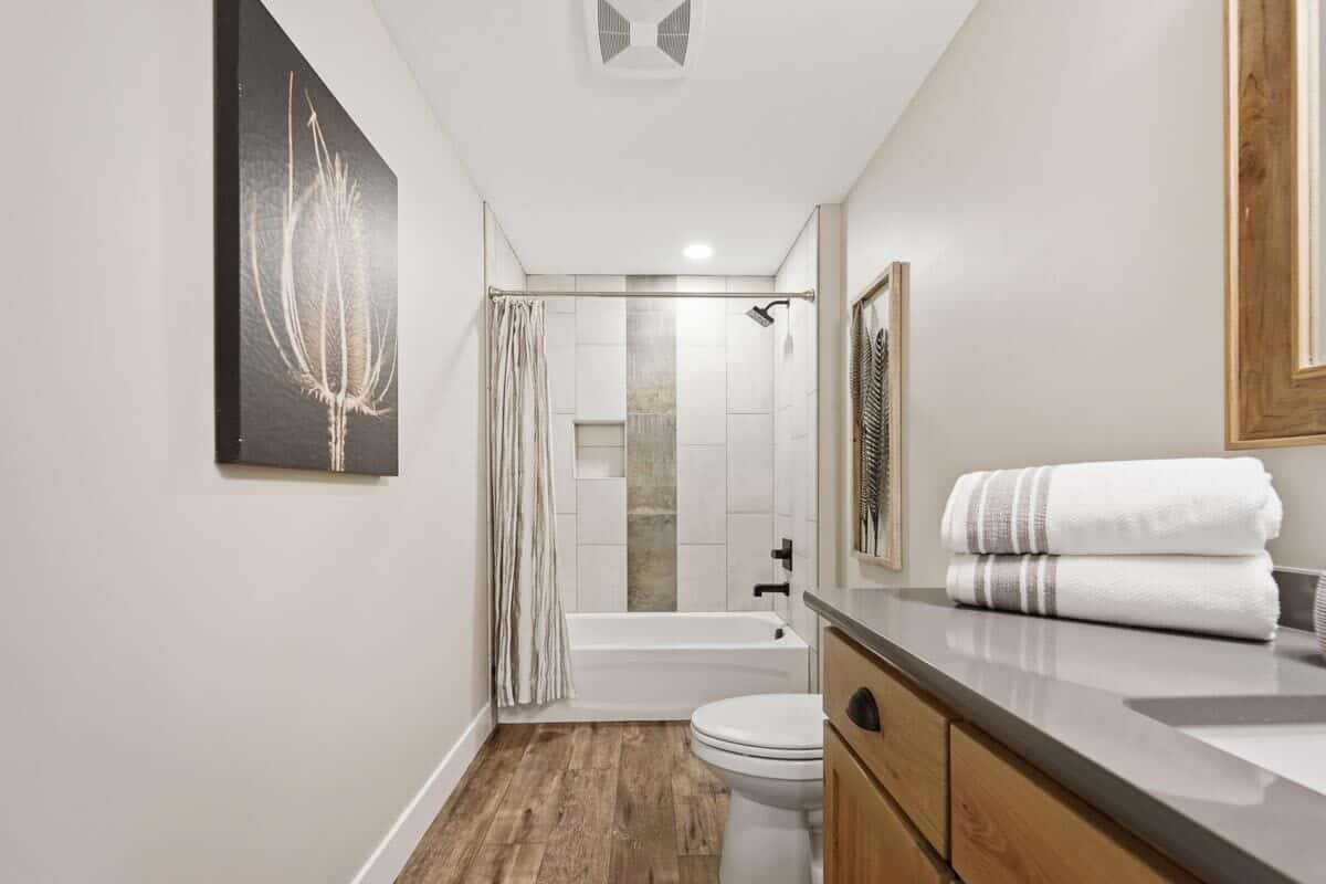 Bathroom with a wooden vanity, a toilet, a tub and shower combo, and interesting artworks.