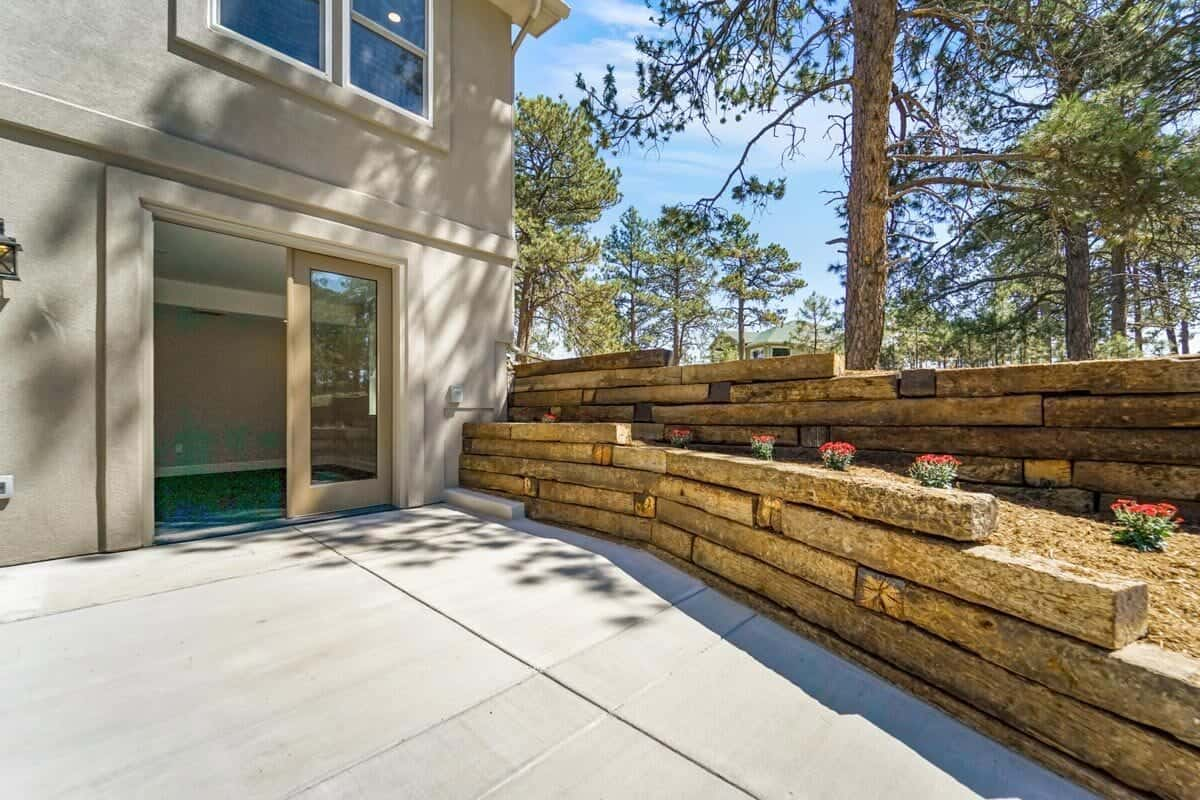 View of the fitness room from the rear patio with brick retaining walls.