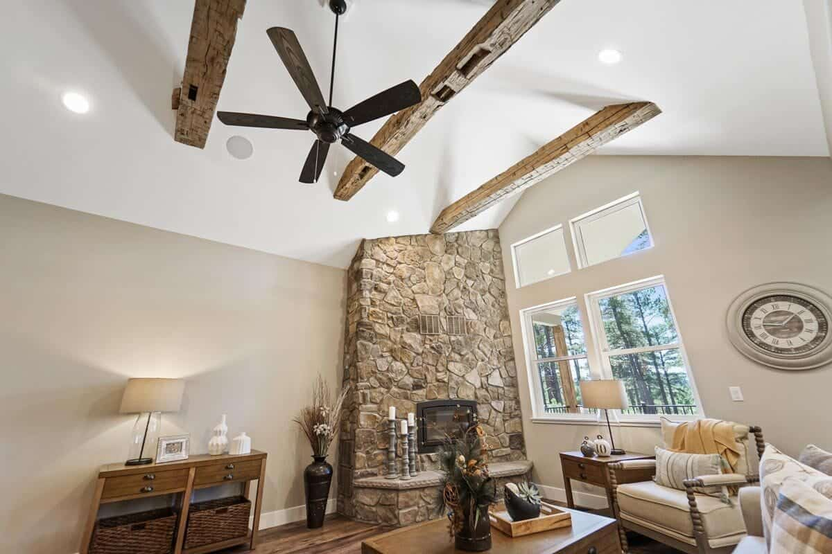 A vaulted ceiling lined with rustic wood beams crowns the recreation room.