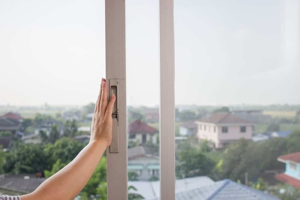 A woman opening up a sliding windows with glass panels.