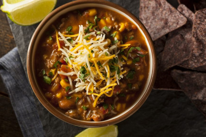 A hearty bowl of Southwest Chicken Soup with cheese toppings.