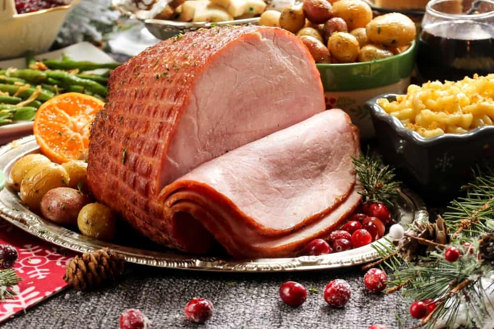 A close look at a sliced glazed ham on a thanksgiving spread.