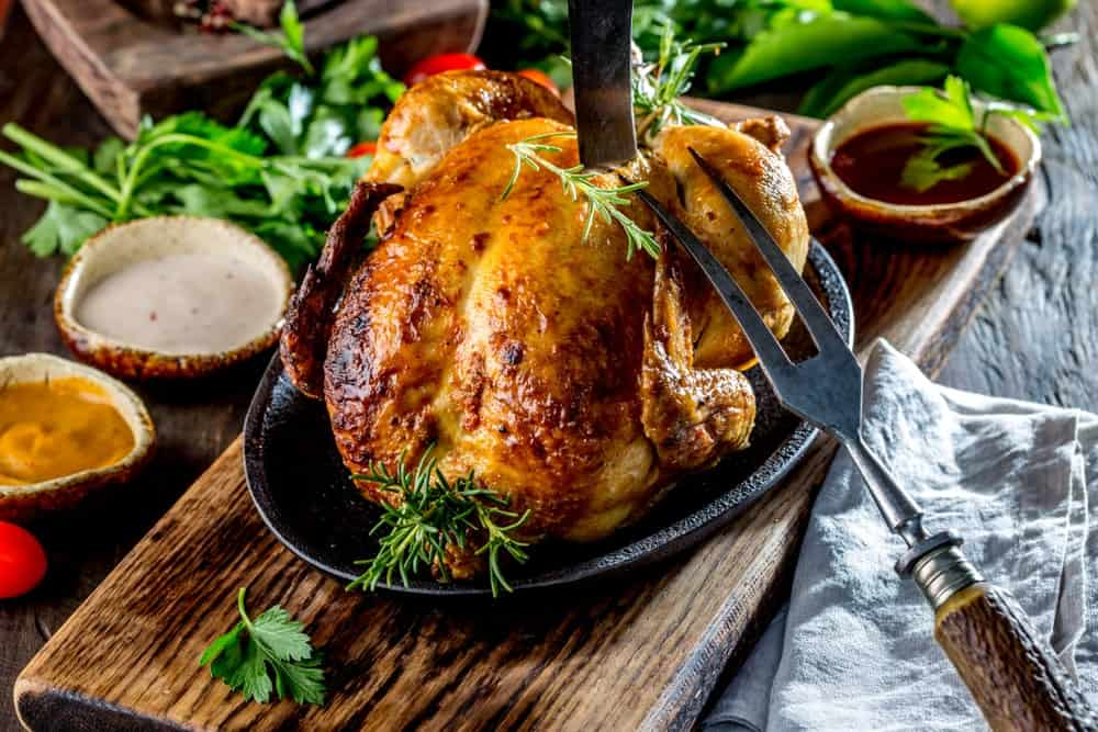 A whole roasted chicken with herbs and dip on the side.