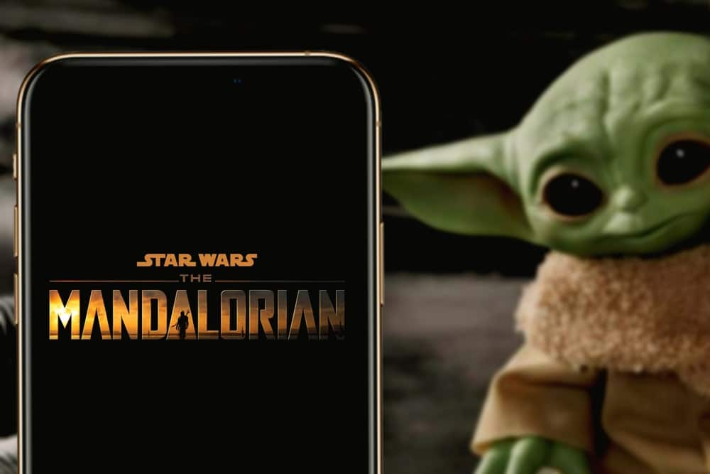 A close look at the Mandalorian Logo with a Baby Yoda Toy on the side.