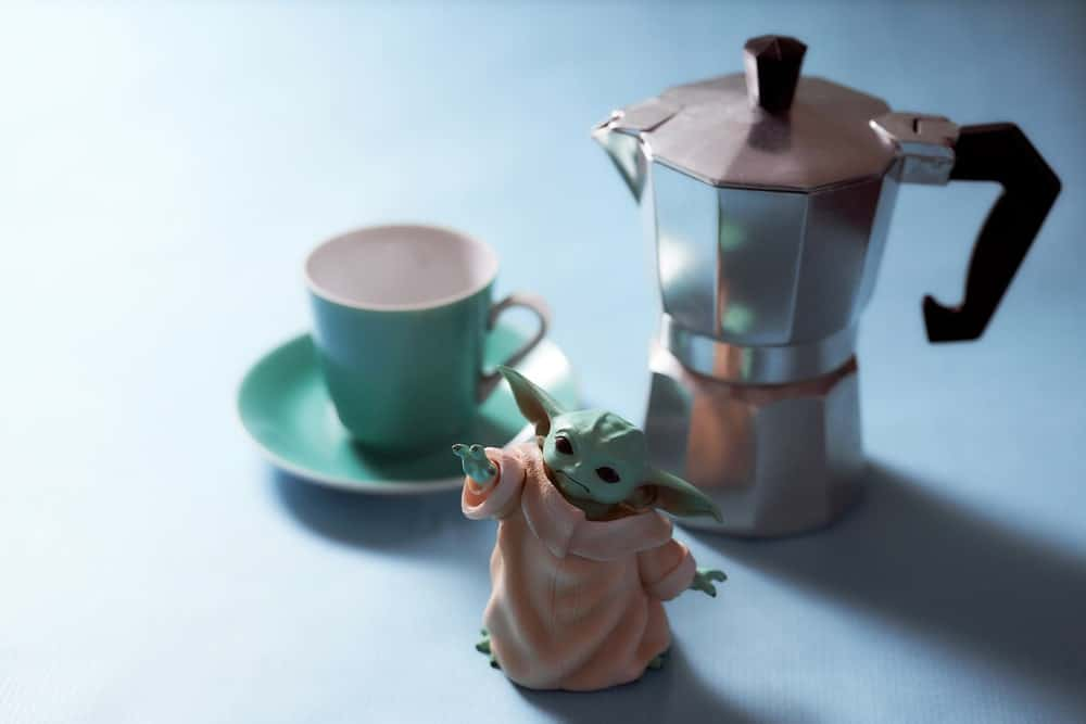 A small Baby Yoda action figure with a tea set.