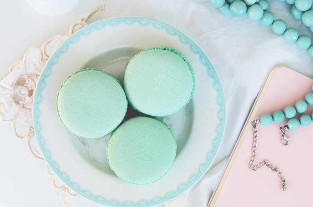 Pieces of pastel blue French Macarons on a saucer.