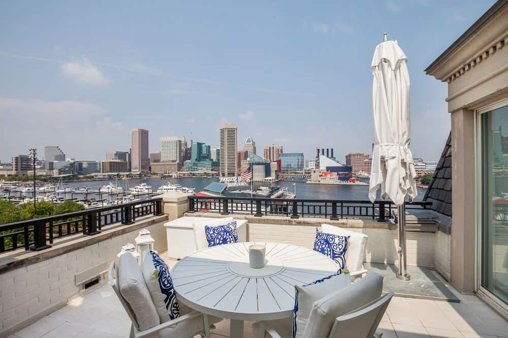 This other balcony is fitted with an outdoor dining area that has a round table and a view of the city skyline. Image courtesy of Toptenrealestatedeals.com.