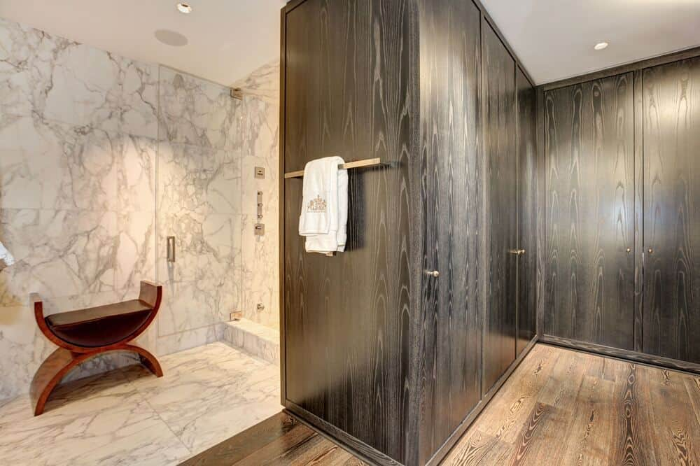 This leads to the glass-enclosed shower area on the far corner with white marble walls and floor. Image courtesy of Toptenrealestatedeals.com.
