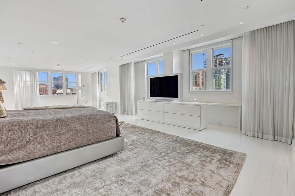 This is the bedroom with a large gray bed on a gray area rug making it stand out against the white tones of the walls, ceiling, floor and the cabinet under the TV. Image courtesy of Toptenrealestatedeals.com.