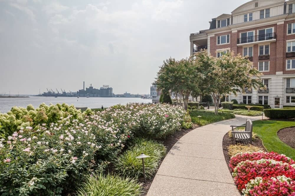This is the paved walkway leading to the penthouse's building adorned with a garden of flowering shrubs and trees. Image courtesy of Toptenrealestatedeals.com.