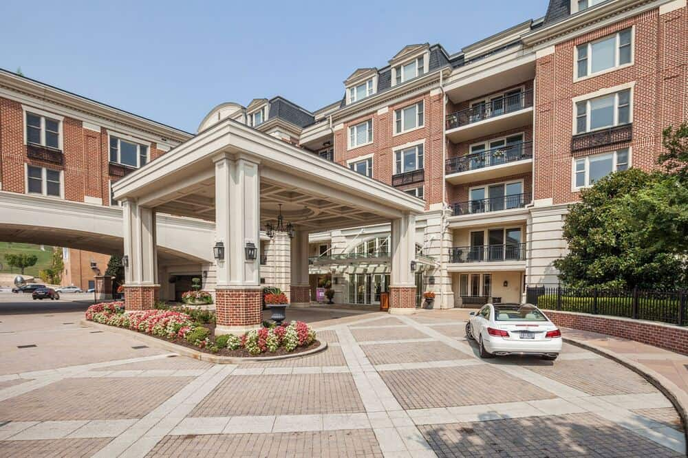 This is the main entrance of the building with a large drop-off area that is covered and has a wide driveway. Image courtesy of Toptenrealestatedeals.com.