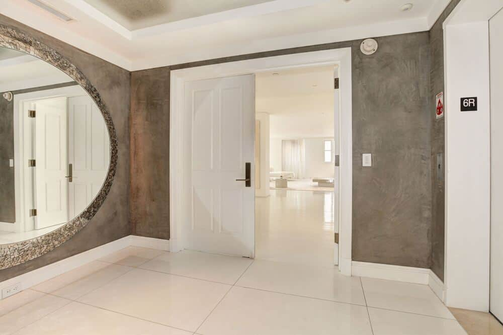 Upon entry of the penthouse, you are welcomed by this simple foyer with bright white wooden doors that match the ceiling. These are then complemented by the large mirror. Image courtesy of Toptenrealestatedeals.com.