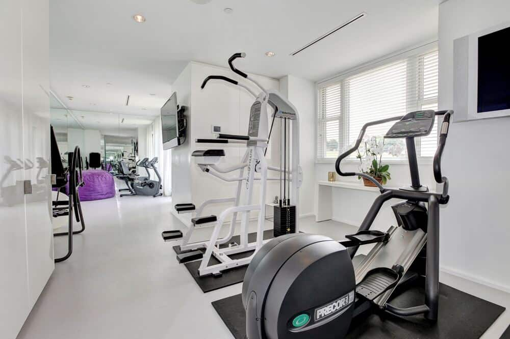 This is the fully equipped home gym with machines that stand out against the surrounding bright walls and ceiling. Image courtesy of Toptenrealestatedeals.com.