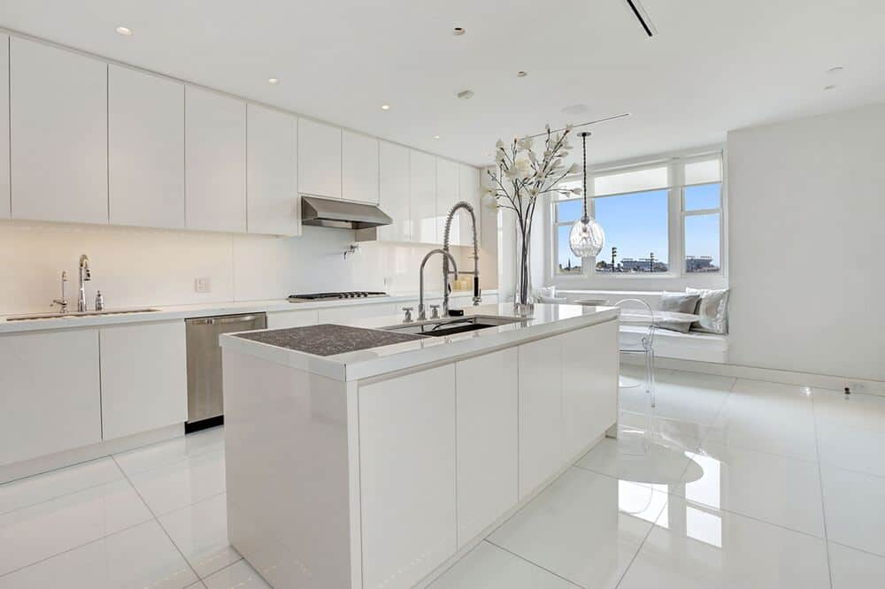 This is the bright white modern kitchen with a large kitchen island that matches the tone of the white-tiled floor and white cabinetry. Image courtesy of Toptenrealestatedeals.com.
