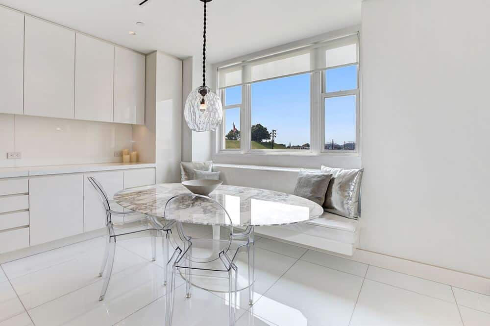 This is the breakfast nook at the far end of the kitchen with a round glass table paired with a cushioned built-in bench under the window. Image courtesy of Toptenrealestatedeals.com.