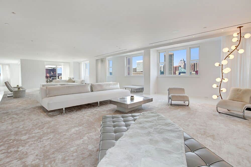 The spacious living room has bright beige walls complemented by windows to brighten up the large L-shaped sofa. Image courtesy of Toptenrealestatedeals.com.