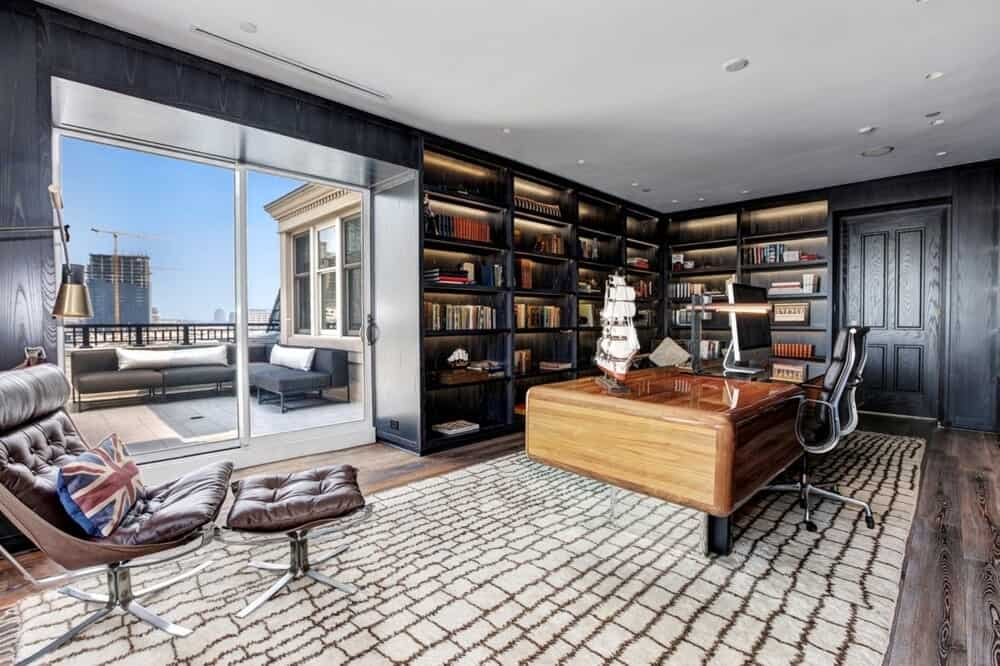 This home office has a large wooden desk with a background of dark built-in bookshelves that are brightened by the window. Image courtesy of Toptenrealestatedeals.com.