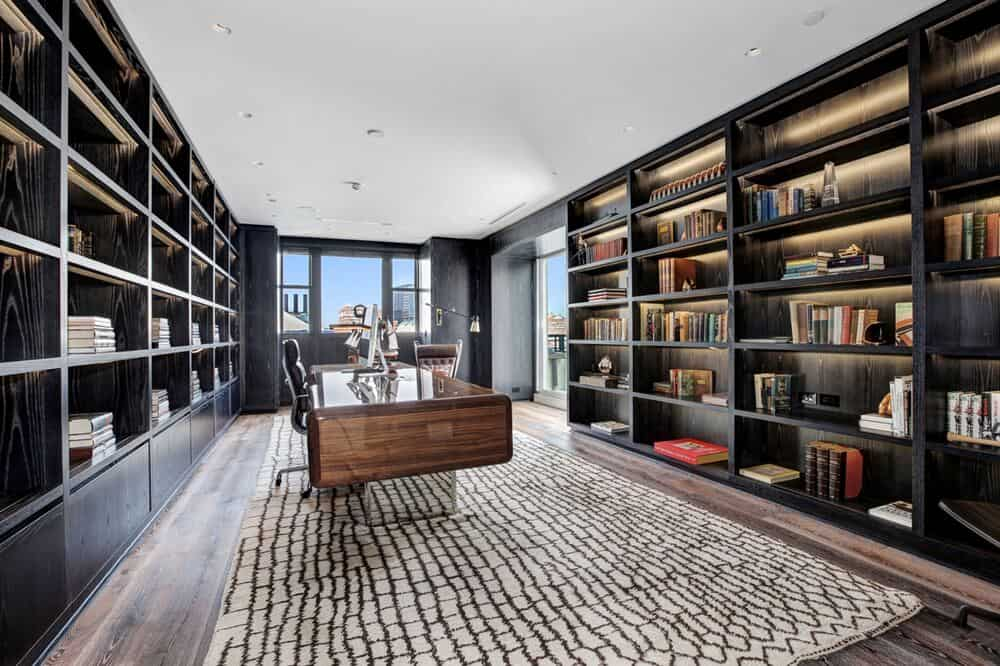 This other home office has a large wooden desk in between of two wide walls filled with built-in bookshelves. The dark tone of the shelves are complemented by the natural lighting. Image courtesy of Toptenrealestatedeals.com.