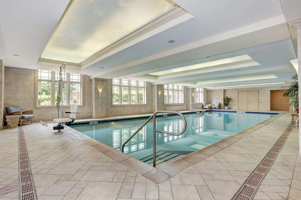 This is the large indoor pool with beige tiles on its surrounding walkways to match the beige ceiling brightened by windows. Image courtesy of Toptenrealestatedeals.com.