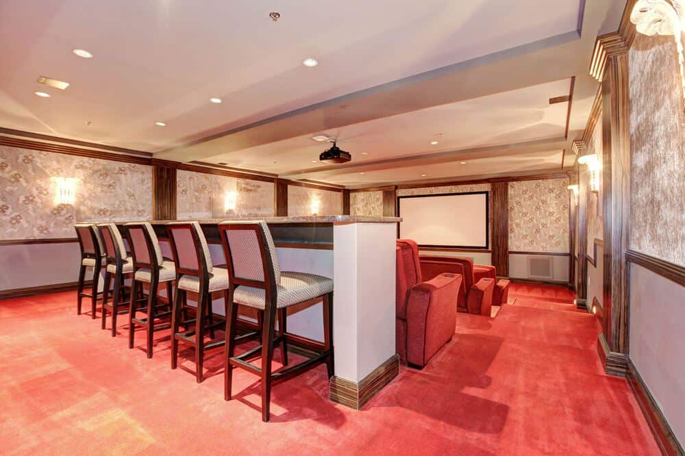 The home theater room has a red carpeted flooring to match the theater-style red chairs across from the large projector screen at the far side of the room. Image courtesy of Toptenrealestatedeals.com.