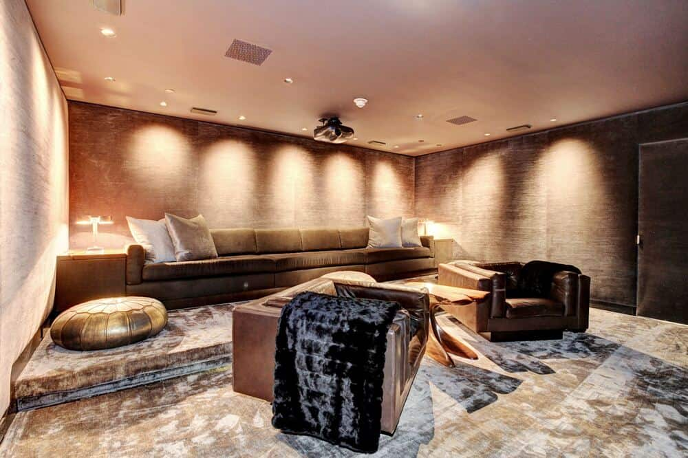 This other home theater room has a more intimate setup that has a sofa and a couple of armchairs paired with side tables and ottomans. Image courtesy of Toptenrealestatedeals.com.