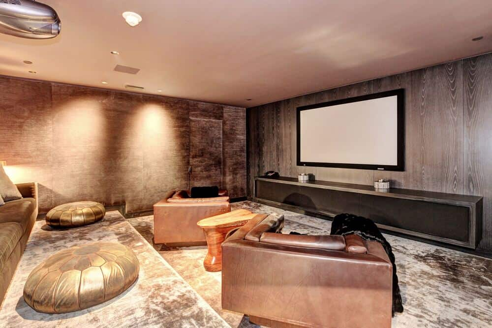 This home theater has a large projector screen above the long entertainment cabinet across from the sofas and armchairs. Image courtesy of Toptenrealestatedeals.com.