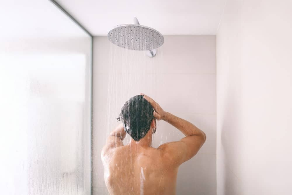 A man bathing under a fixed showerhead.