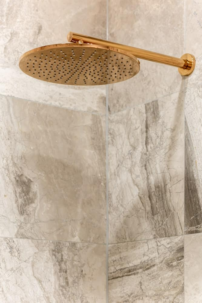 This is a close look at a golden overhead fixed showerhead.