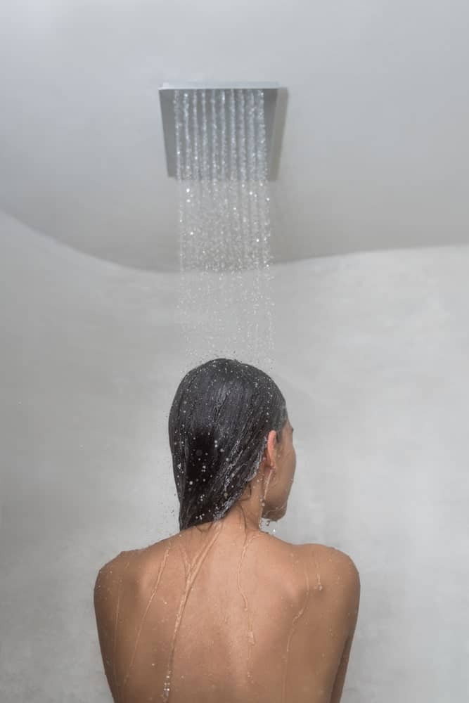 A woman is bathing underneath a showerhead that is mounted on the ceiling.
