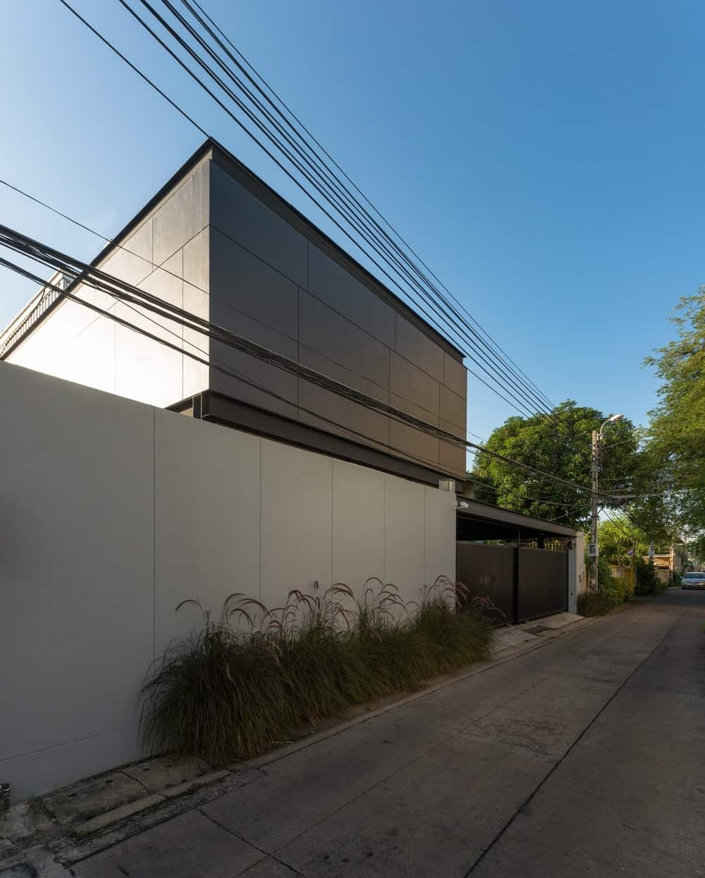 This is a front view of the house from the street showcasing the modern tones and wall panels of the house adorned with a row of shrubs on the side of the bright concrete wall by the entrance.