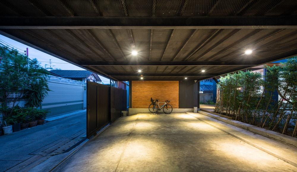 This is the interior of the car port. You can see here the modern lighting, the black metal beams and a decorative wall on the side.