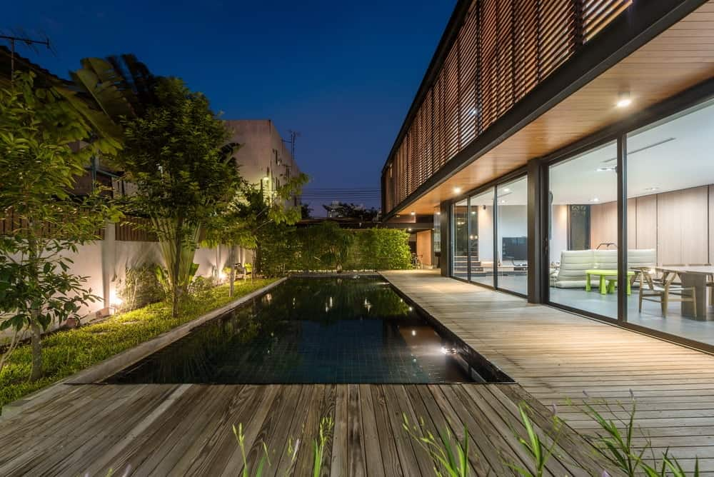 This view of the poolside area showcases more of the landscaping that extends to the side with grass lawn, tall trees and mood lighting that makes them stand out.