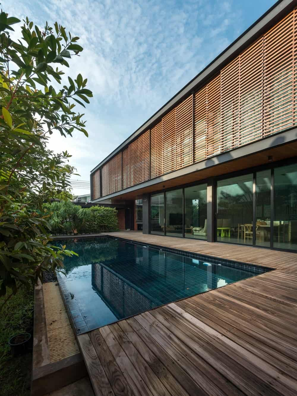 The wooden slats of the second floor panels match the walkway flooring on the sides of the infinity pool.