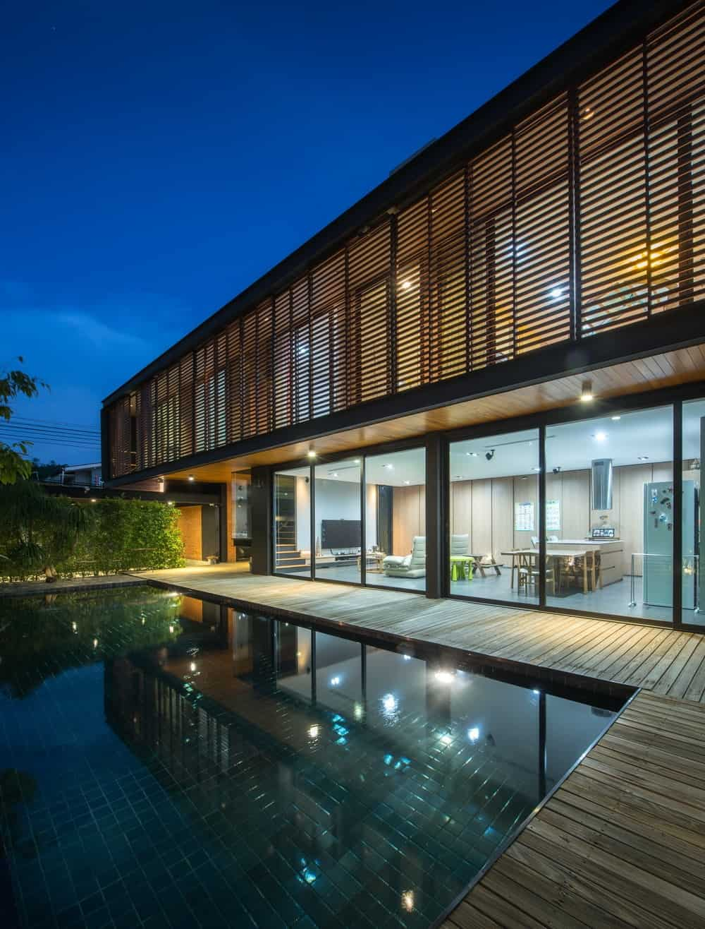 This is a view of the house from the vantage of the swimming pool showcasing the warm lights that escape through the glass walls and the wooden panels of the second floor.