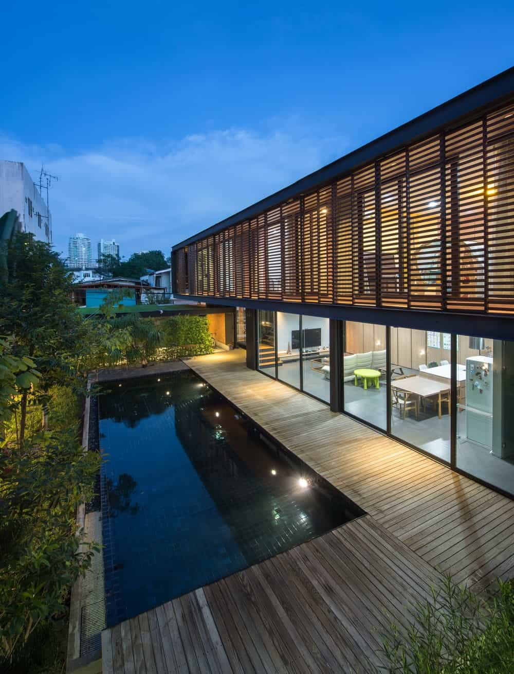 This view of the house makes the interiors of the ground floor show up with its lighting and glass wall.
