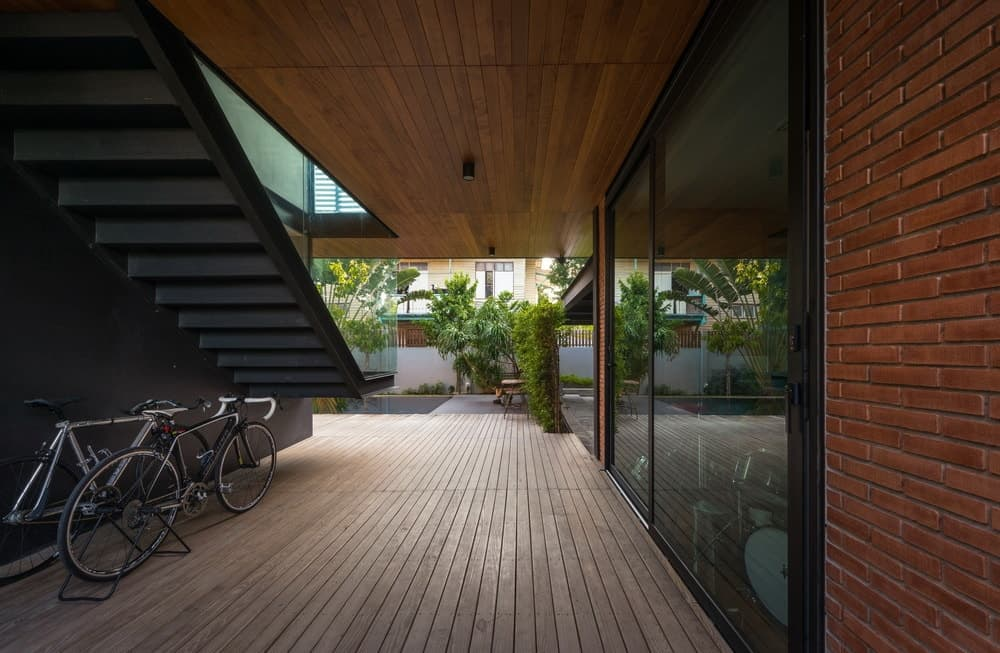 The car port leads to this walkway on the side of the house with glass doors, walls and a wooden flooring.
