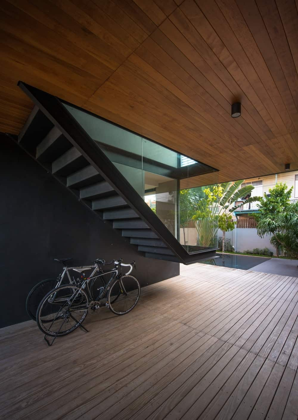 This area of the staircase and wooden flooring leads to the poolside area on the far side.