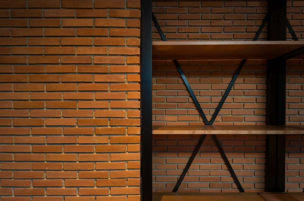 This is a close look at the shelf of the dining room with metal beam frames , wooden shelves and red brick wall.