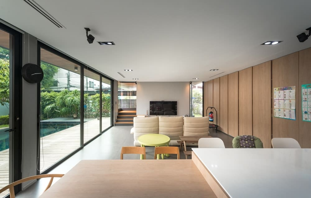 A few steps from the beige sofa is the large wooden kitchen island with a white countertop illuminated by the natural lights of the glass walls.