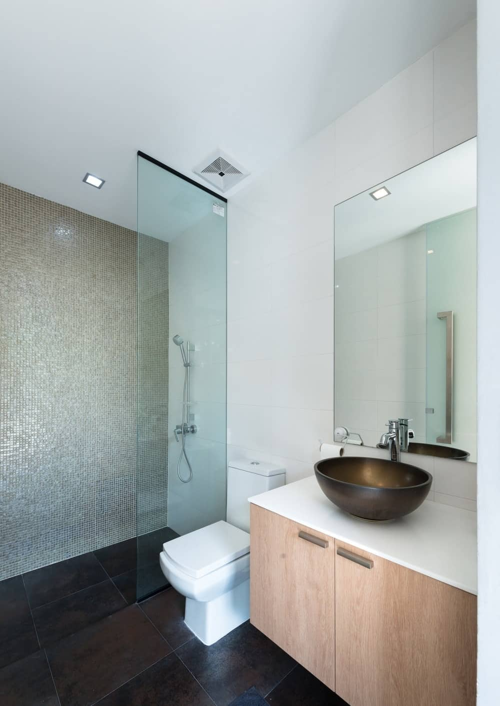 This bathroom has a glass-enclosed shower area on the side of the toilet with a dark floor.