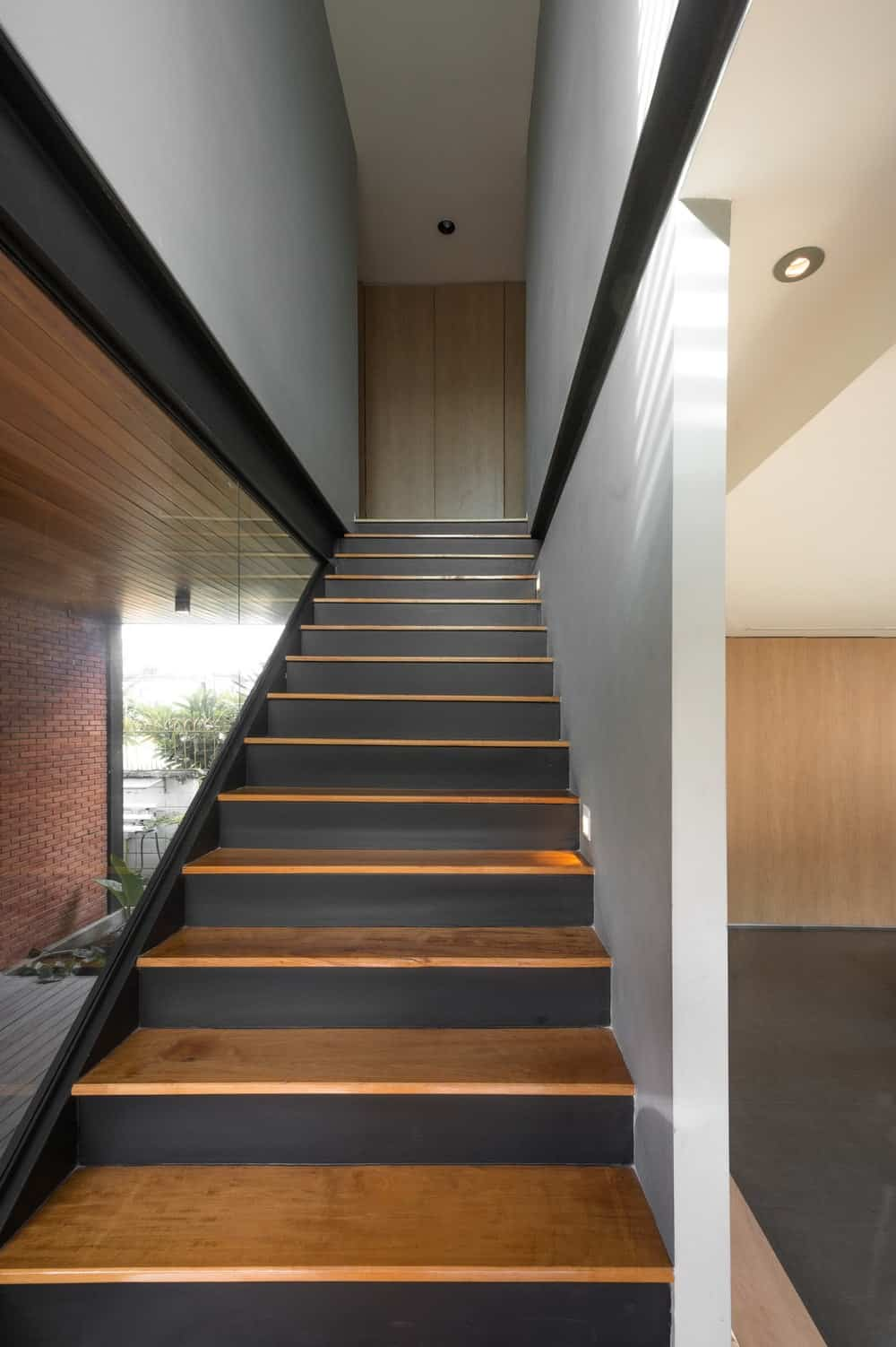 This is a close look at the staircase with wooden steps, metal beams and glass walls.