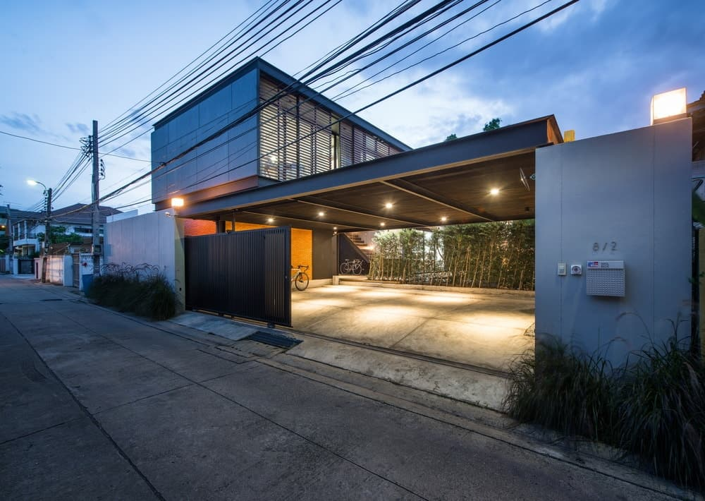 The car port is illuminated by modern lighting attached to the ceiling of the car port matching with the warm glow of the exterior lights.