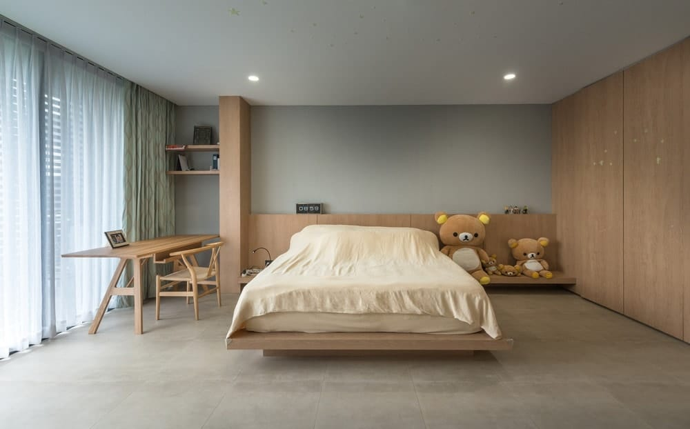 This is the spacious bedroom with a wooden floating platform bed attached to a large wooden structure on the far wall that houses the bedside table, shelves and desk for the study area.