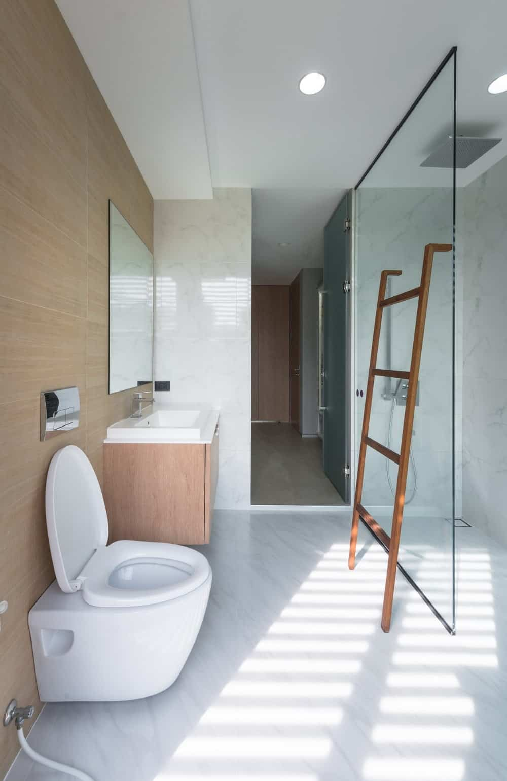 The bathroom has a wooden wall behind the modern white toilet beside the wooden vanity.