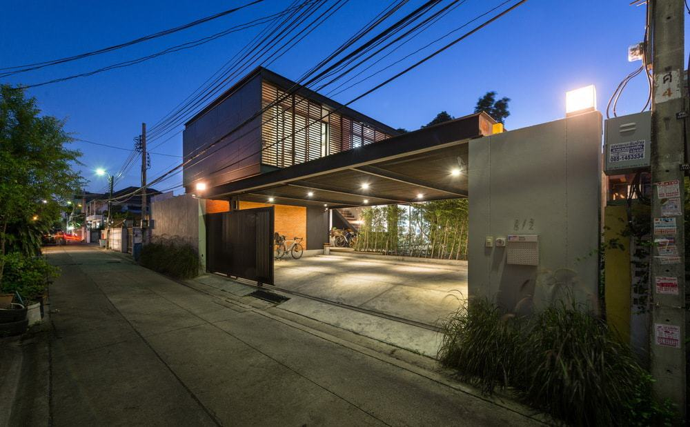 The large gate retracts to open to a wide car port that is topped with a wide ceiling made of dark metal that matches the gate and house exterior.