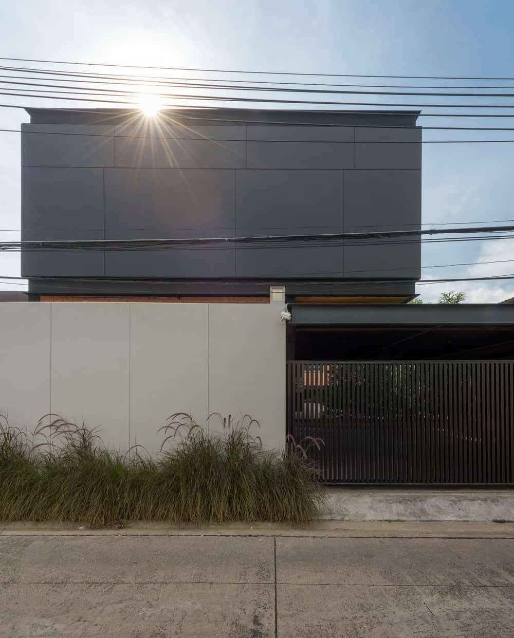 The house has simple white, black and gray tones adorned with a row of shrubs that bring color to the exteriors.